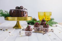 Dark chocolate cake with cookies and cupcakes berries on white wooden background Stock Photo