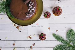 Dark chocolate cake with cookies and cupcakes berries on white wooden background. Lettering. Postcard Royalty Free Stock Photography