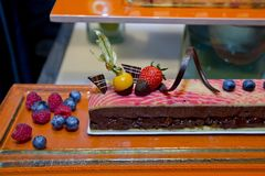 Dark chocolate cake with fresh fruit topping and around display Stock Image