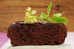 Dark chocolate cake with linden blossoms on wooden background Royalty Free Stock Photo