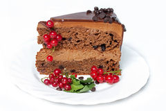 Dark chocolate cake with red currants and green leaves Stock Photography