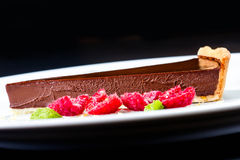 Dark chocolate cake. Slice of chocolate layer cake with red be Stock Photo
