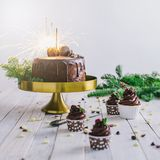 Dark chocolate cake with sparklers and cupcakes berries on white wooden background. Dark chocolate cake with sparklers and cupcakes with berries on white wooden Royalty Free Stock Photo