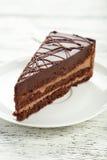 Dark chocolate cake on white wooden background. Royalty Free Stock Photo
