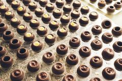 Dark chocolate candies are arranged in rows in special shapes. Cooking handmade chocolates. Selective focus. royalty free stock photo