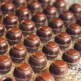 Dark chocolate candies are arranged in rows in special shapes. Cooking handmade chocolates. Selective focus. royalty free stock photos