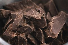 Dark chocolate chunks in steel bowl on table. Shallow focus Royalty Free Stock Images