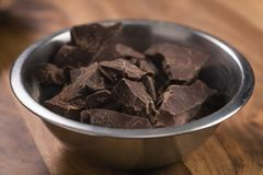 Dark chocolate chunks in steel bowl on table. Shallow focus Stock Photos