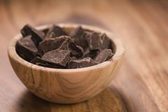 Dark chocolate chunks in wood bowl on table. Shallow focus Stock Photography