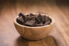 Dark chocolate chunks in wood bowl on table. Shallow focus Stock Image