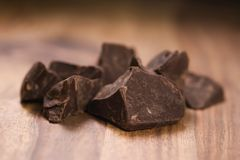 Dark chocolate chunks on wood table. Shallow focus Royalty Free Stock Photo