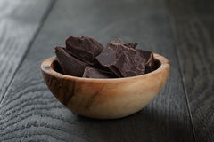 Dark chocolate chunks in wooden bowl Royalty Free Stock Image