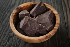 Dark chocolate chunks in wooden bowl Stock Photo