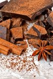 Dark chocolate with cinnamon stick, anise stars and cocoa. Selective focus Stock Photo