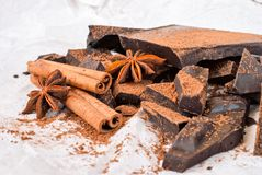 Dark chocolate with cinnamon stick, anise stars and cocoa. Selective focus Royalty Free Stock Photography