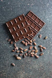 Dark chocolate and cocoa beans Stock Images