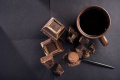 Dark chocolate and cocoa powder. Large pieces of dark chocolate and cocoa powder and coffee cup on black table stock photos
