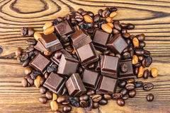 Dark chocolate cubes, coffee beans, peanuts and raisins on wooden table, top view Stock Photography
