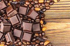 Dark chocolate cubes, coffee beans, peanuts and raisins on wooden table, top view Royalty Free Stock Image