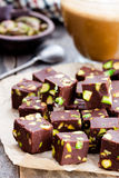 Dark  chocolate cubes  with pistachios and cup of coffee on woode. Dark  chocolate cubes with pistachios and cup of coffee on wooden background Stock Image