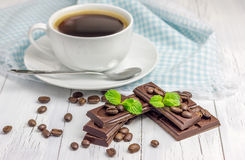 Dark chocolate with a cup of coffee. Dark chocolate decorated with coffee beans and mint with a cup of coffee Royalty Free Stock Image