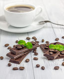 Dark chocolate decorated with coffee beans and cup of coffee. Dark chocolate decorated with coffee beans and a cup of coffee Stock Image