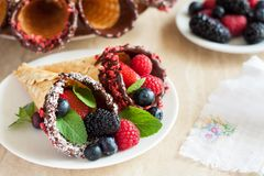 Dark Chocolate-Dipped Waffle Cones with berries. Dark Chocolate-Dipped Waffle Cones filled fresh berries on light background Royalty Free Stock Image
