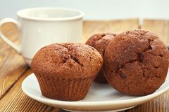Dark chocolate dough muffin on the background of an old wooden table stock photos