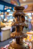 Dark chocolate fondue fountain completely melted and flowing dow. N at dessert section in dinner buffet line Stock Photography