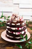 Dark chocolate layered cake with whipped mascarpone cream, chocolate sauce, cherry syrup decorated with sweet marble meringues on. A plate on a wooden table stock photos