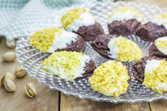 Dark chocolate madeleines, covered with white chocolate and pistachio. Dark chocolate madeleines covered with white chocolate and pistachio royalty free stock photography