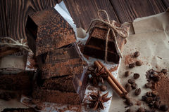 Dark chocolate on paper on wooden table with coffee bean, cocoa Stock Photo