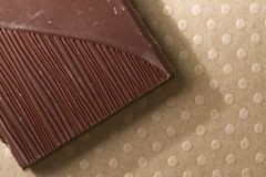 Dark chocolate piece. Close-up of dark chocolate piece on dotted ground royalty free stock photo