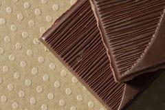 Dark chocolate pieces. Close-up of dark chocolate piece on dotted ground royalty free stock photos