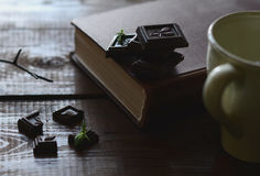 Dark chocolate pieces, a book and cup on breakfast table Stock Photo