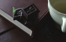 Dark chocolate pieces, a book and cup on breakfast table Stock Image