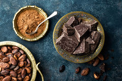 Dark chocolate pieces crushed and cocoa beans, culinary background Royalty Free Stock Photo