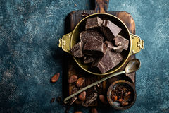 Dark chocolate pieces crushed and cocoa beans, culinary background Stock Image
