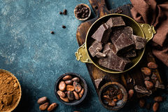 Dark chocolate pieces crushed and cocoa beans, culinary background Stock Photo