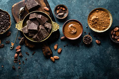 Dark chocolate pieces crushed and cocoa beans, culinary background Stock Photos