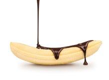 Dark chocolate is poured on the ripe banana Stock Photo