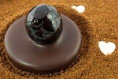 Dark chocolate pralines with candied cherries on barley coffee background. Chocolate pralines with candied cherries royalty free stock photo