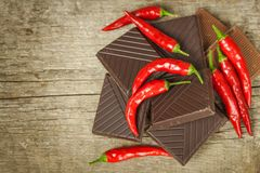 Dark chocolate and red chili peppers. Selling spicy chocolate. Crazy taste. Royalty Free Stock Photo