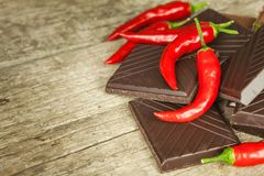 Dark chocolate and red chili peppers. Selling spicy chocolate. Crazy taste. Stock Photo