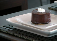 Dark chocolate round cake. Dark chocolate cake with cream topping Royalty Free Stock Images