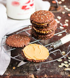 Dark chocolate sandwich cookies with oat flakes and peanut butter cream stacked on a cooling rack on a wooden table Stock Photo