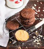 Dark chocolate sandwich cookies with oat flakes and peanut butter cream stacked on a cooling rack on a wooden table Stock Photography