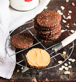 Dark chocolate sandwich cookies with oat flakes and peanut butter cream stacked on a cooling rack on a wooden table Royalty Free Stock Photos