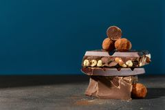 Dark chocolate stack and truffle chocolates on blue background. With copy space Royalty Free Stock Photo