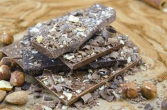 Dark chocolate stacked on a cocoa sprinkled table with nuts and stock photos